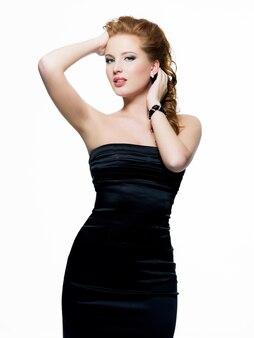 Mulher jovem e bonita sensual em vestido preto posando
