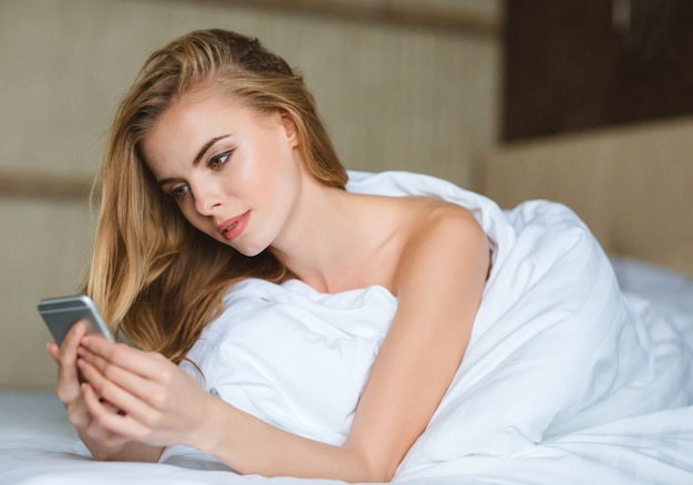 Mulher jovem e bonita sensual usando smartphone deitada na cama