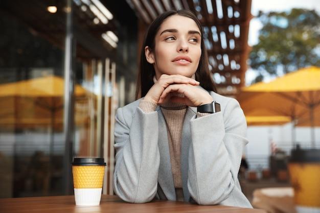Mulher jovem e bonita sentada com casaco e smartwatch esperando em um café.