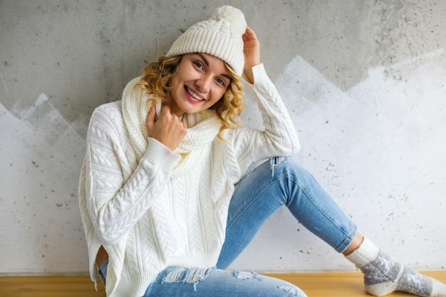 Mulher jovem e bonita sentada contra a parede usando jeans e suéter branco