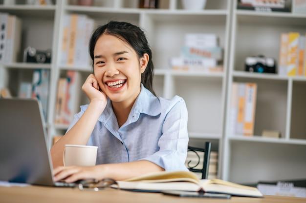 Mulher jovem e bonita sentada e usando o laptop e o livro didático para trabalhar ou aprender on-line, segurando a caneca de café na mão e sorrindo com felicidade