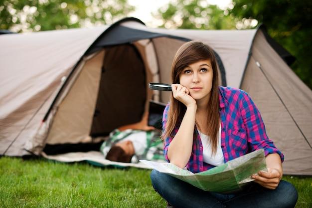 Mulher jovem e bonita sentada em frente a uma tenda