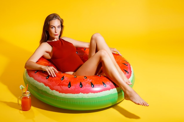 Mulher jovem e bonita sentada em um anel de melancia inflável com coquetel isolado em fundo amarelo