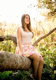 Mulher jovem e bonita sentada em um galho de árvore no campo em um dia ensolarado