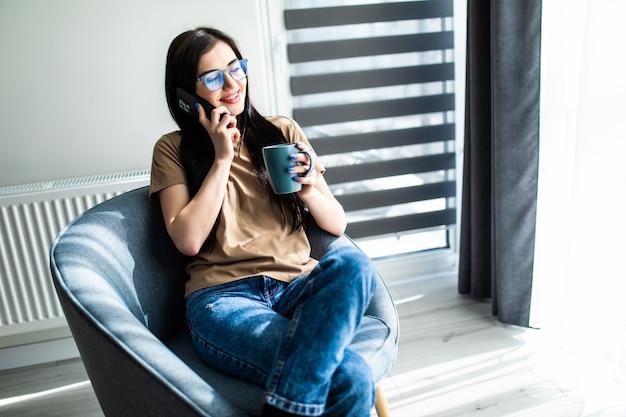 Mulher jovem e bonita sentada na cadeira falando ao telefone enquanto toma uma xícara de café