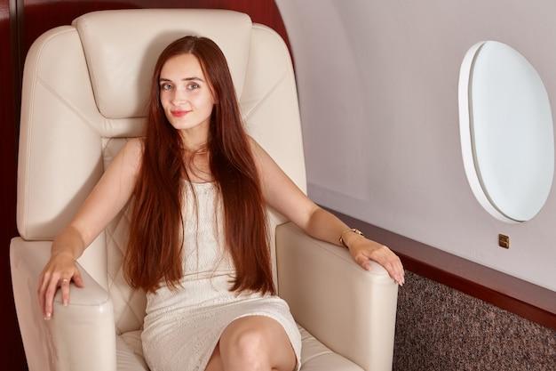Mulher jovem e bonita sentada na classe executiva dentro do avião na poltrona
