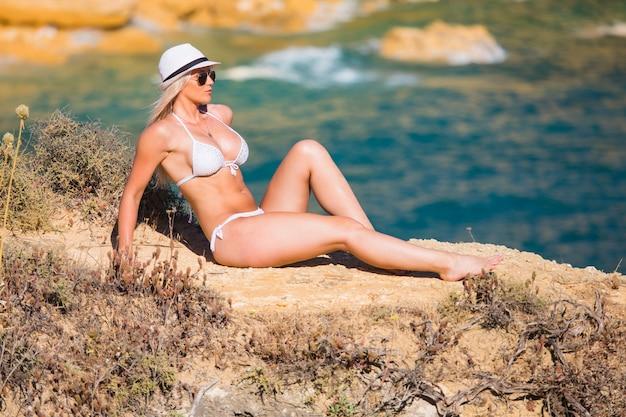 Mulher jovem e bonita sentada na pedra à beira-mar