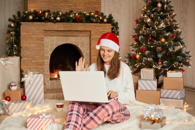 Mulher jovem e bonita sentada no chão com o laptop sobre os joelhos, tendo a videochamada, cumprimentando alguém e acenando com a mão, vestindo calça xadrez, camisa branca e chapéu de papai noel.