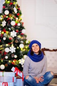 Mulher jovem e bonita sentada no chão contra uma árvore de natal com guirlandas iluminadas e bolas
