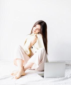 Mulher jovem e bonita sentada no chão fazendo um projeto freelance no laptop, usando o computador