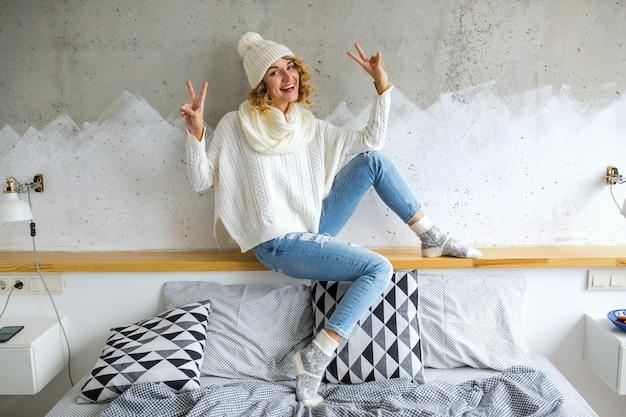 Mulher jovem e bonita sentada no quarto contra a parede usando um suéter branco