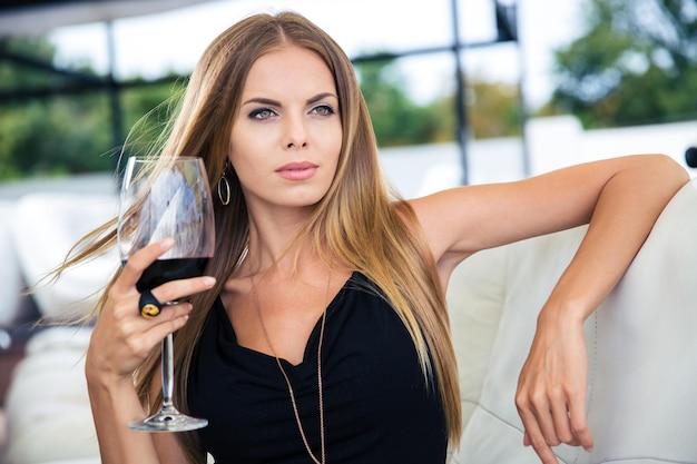 Mulher jovem e bonita sentada no restaurante com uma taça de vinho tinto