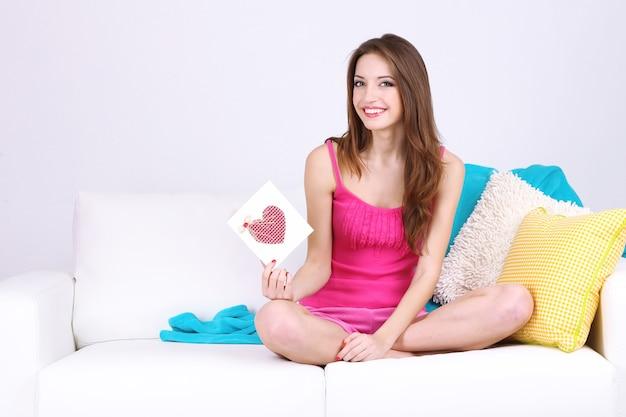 Mulher jovem e bonita sentada no sofá com o cartão na superfície cinza