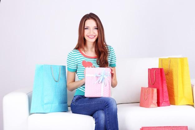 Mulher jovem e bonita sentada no sofá com sacolas de compras e caixa de presente