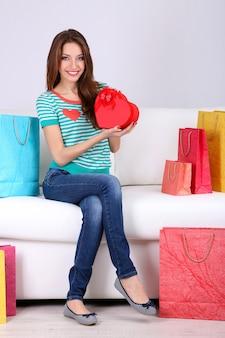 Mulher jovem e bonita sentada no sofá com sacolas de compras e uma caixa de presente em um fundo cinza