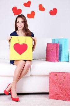 Mulher jovem e bonita sentada no sofá com sacolas de compras em fundo cinza