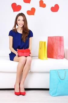 Mulher jovem e bonita sentada no sofá com sacolas de compras