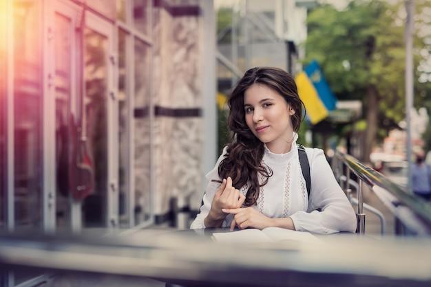 Mulher jovem e bonita sentada perto de um café no centro da cidade e posando, aproveite o estilo de vida de verão