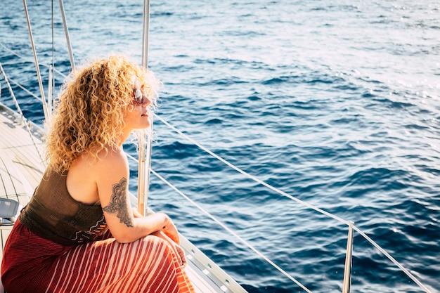 Mulher jovem e bonita sente-se e sorria no convés do iate, olhando para o mar e o sol, aproveitando a liberdade e o estilo de vida