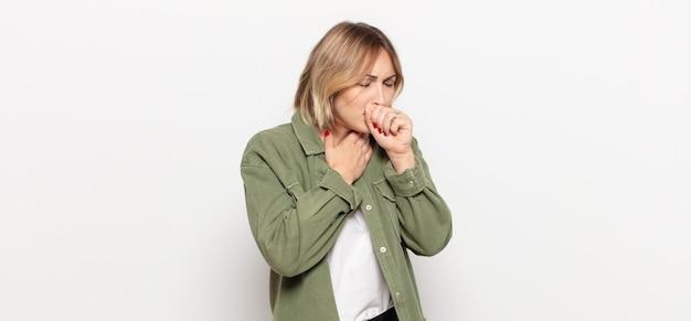 Mulher jovem e bonita sentindo-se doente com dor de garganta e sintomas de gripe, tosse com a boca coberta