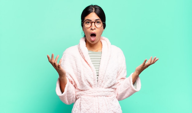 Mulher jovem e bonita sentindo-se extremamente chocada e surpresa, ansiosa e em pânico, com um olhar estressado e horrorizado. conceito de pijama
