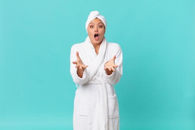 Mulher jovem e bonita sentindo-se extremamente chocada e surpresa, usando roupão de banho após o banho