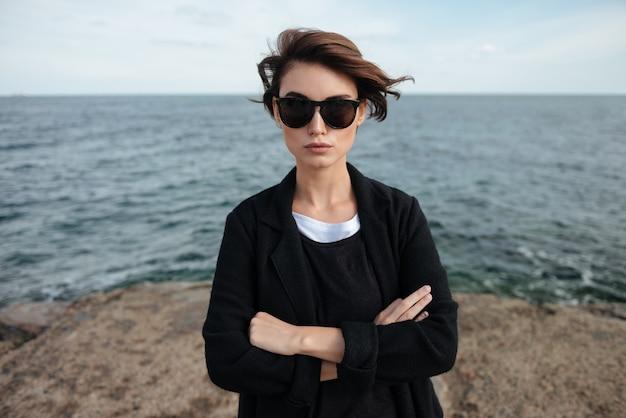 Mulher jovem e bonita séria de óculos escuros em pé com os braços cruzados à beira-mar