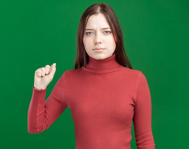 Mulher jovem e bonita séria olhando para frente fazendo gesto de bater na parede verde