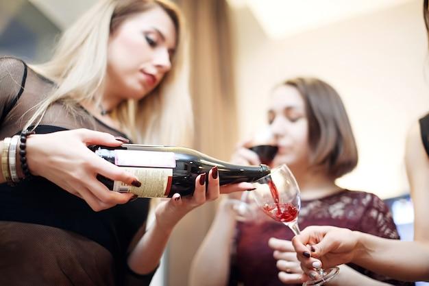 Mulher jovem e bonita servindo vinho tinto para uma amiga na festa de ano novo