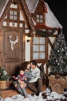 Mulher jovem e bonita, seu marido bonito e seu filho pequeno bonito posando na escada decorada para a casa de natal