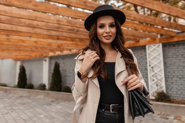 Mulher jovem e bonita sexy com um sorriso doce em um chapéu da moda e um casaco clássico cinza com uma bolsa de couro preta caminha pela cidade
