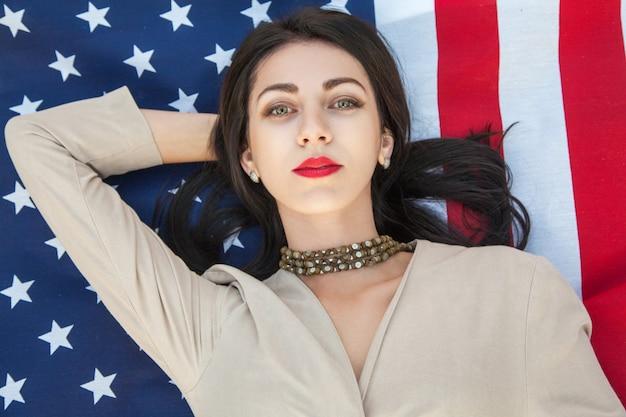 Mulher jovem e bonita sexy com um vestido clássico deitada na bandeira americana no parque.