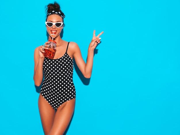 Mulher jovem e bonita sexy hipster sorridente em óculos de sol. garota de maiô de ervilhas de verão maiô. posando perto da parede azul, bebendo bebida smoozy cocktail fresca. mostra o sinal de paz