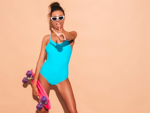 Mulher jovem e bonita sexy hipster sorridente em óculos de sol. menina na moda em trajes de banho de moda praia de verão. fêmea positiva enlouquecendo com skate centavo rosa, isolado na parede bege