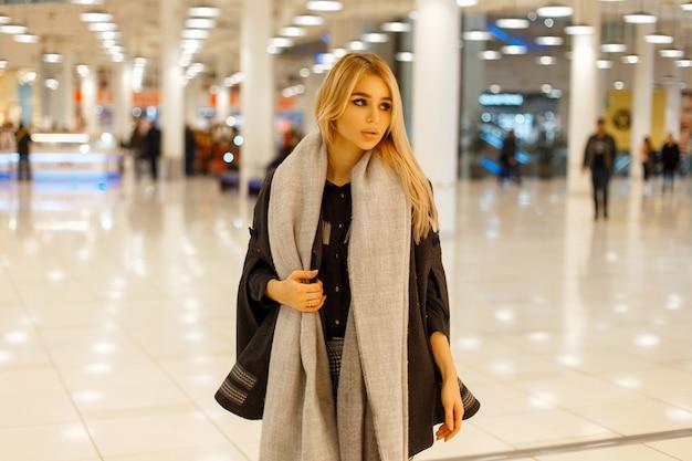 Mulher jovem e bonita sexy na moda elegante casaco com lenço cinza posando em um shopping