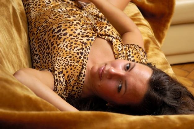 Mulher jovem e bonita sexy posando no sofá de couro. garota com vestido curto de tigre. o tema juventude, atratividade e sexualidade.