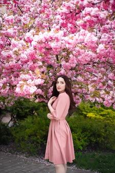 Mulher jovem e bonita sob a árvore-de-rosa florida.