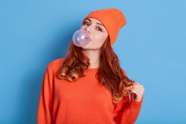 Mulher jovem e bonita soprando chiclete enquanto posa isolada sobre uma parede azul