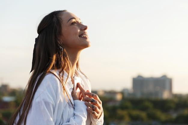 Mulher jovem e bonita sorri concurso permanente no telhado nos raios do sol de noite