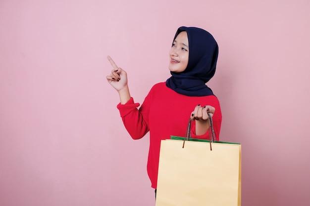 Mulher jovem e bonita sorridente apontando algo vestindo uma camiseta vermelha, segurando uma sacola de compras