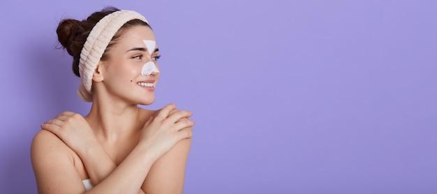 Mulher jovem e bonita sorridente com a pele limpa e perfeita olhando sonhadoramente para o lado e tocando seu ombro nu, fazendo procedimentos de beleza