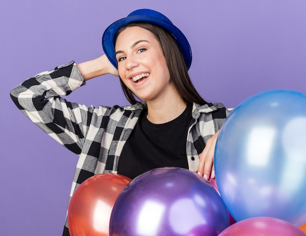 Mulher jovem e bonita sorridente com chapéu de festa em pé atrás de balões, colocando a mão na cabeça isolada na parede azul