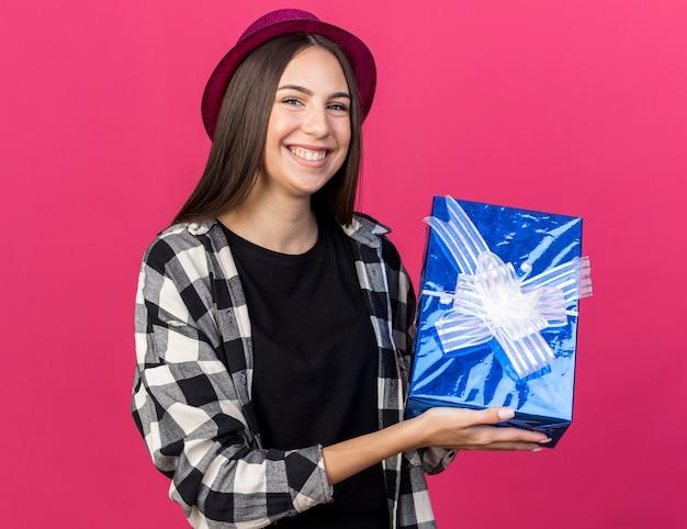 Mulher jovem e bonita sorridente com chapéu de festa segurando uma caixa de presente isolada na parede rosa