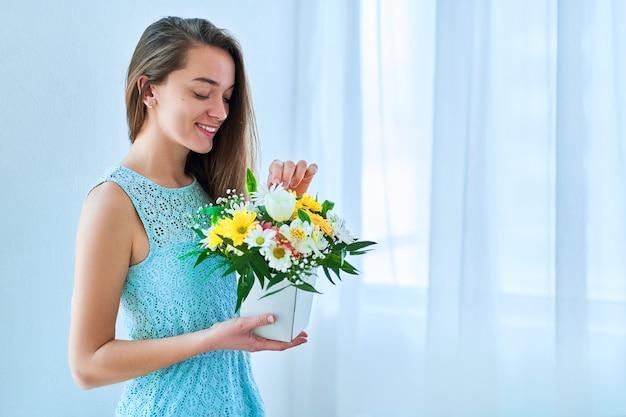 Mulher jovem e bonita sorridente com flores coloridas brilhantes e decorativas.
