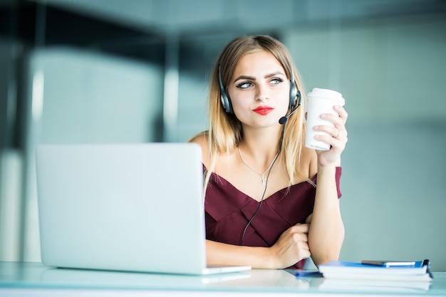 Mulher jovem e bonita sorridente com fones de ouvido e uma xícara de café olhando para o escritório
