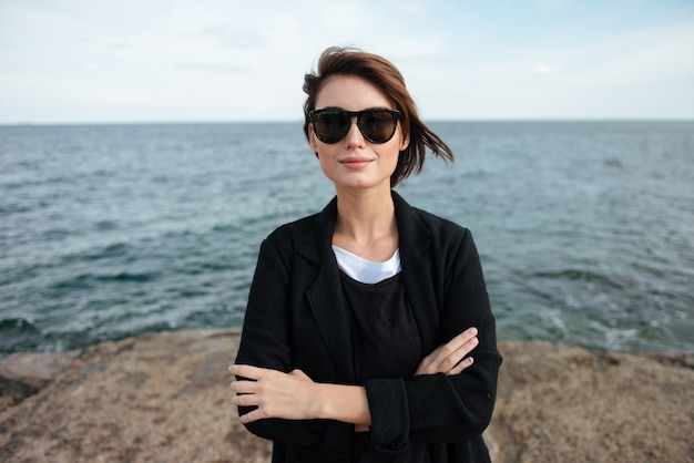 Mulher jovem e bonita sorridente com óculos de sol em pé com as mãos postas perto do mar