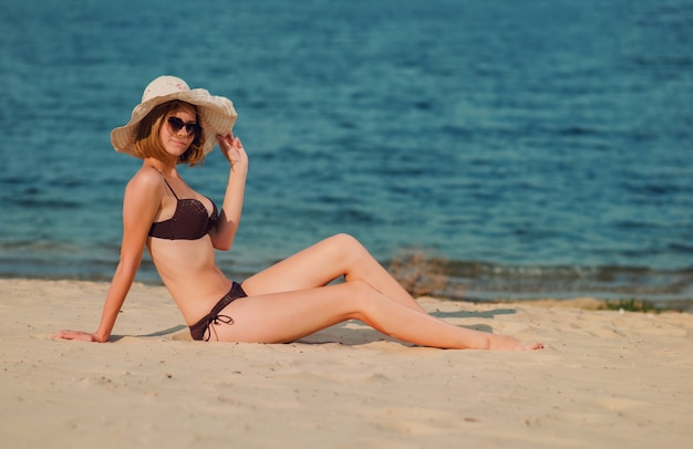 Mulher jovem e bonita sorridente com óculos de sol na praia, sentada na areia dourada