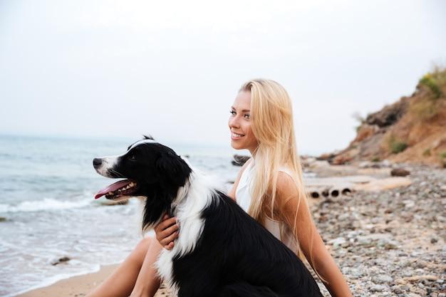 Mulher jovem e bonita sorridente com um cachorro sentado na praia e pensando
