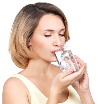 Mulher jovem e bonita sorridente com um copo d'água branco