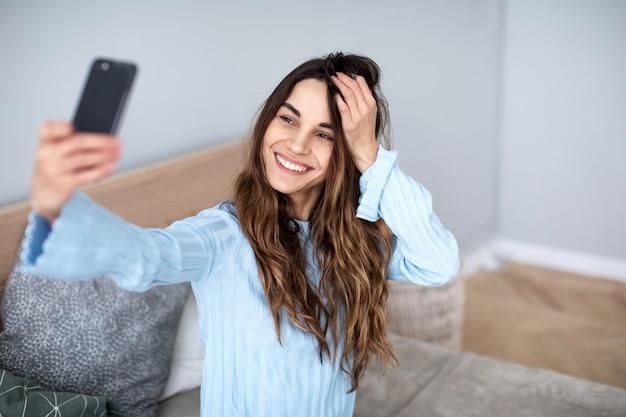 Mulher jovem e bonita sorridente com um telefone nas mãos tira uma selfie. estilo de vida.